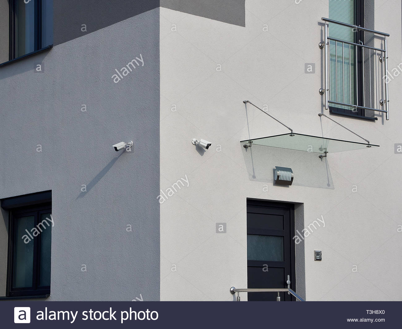 A view of the corner of a white industrial building with two security cameras, doors and windows. - Stock Image