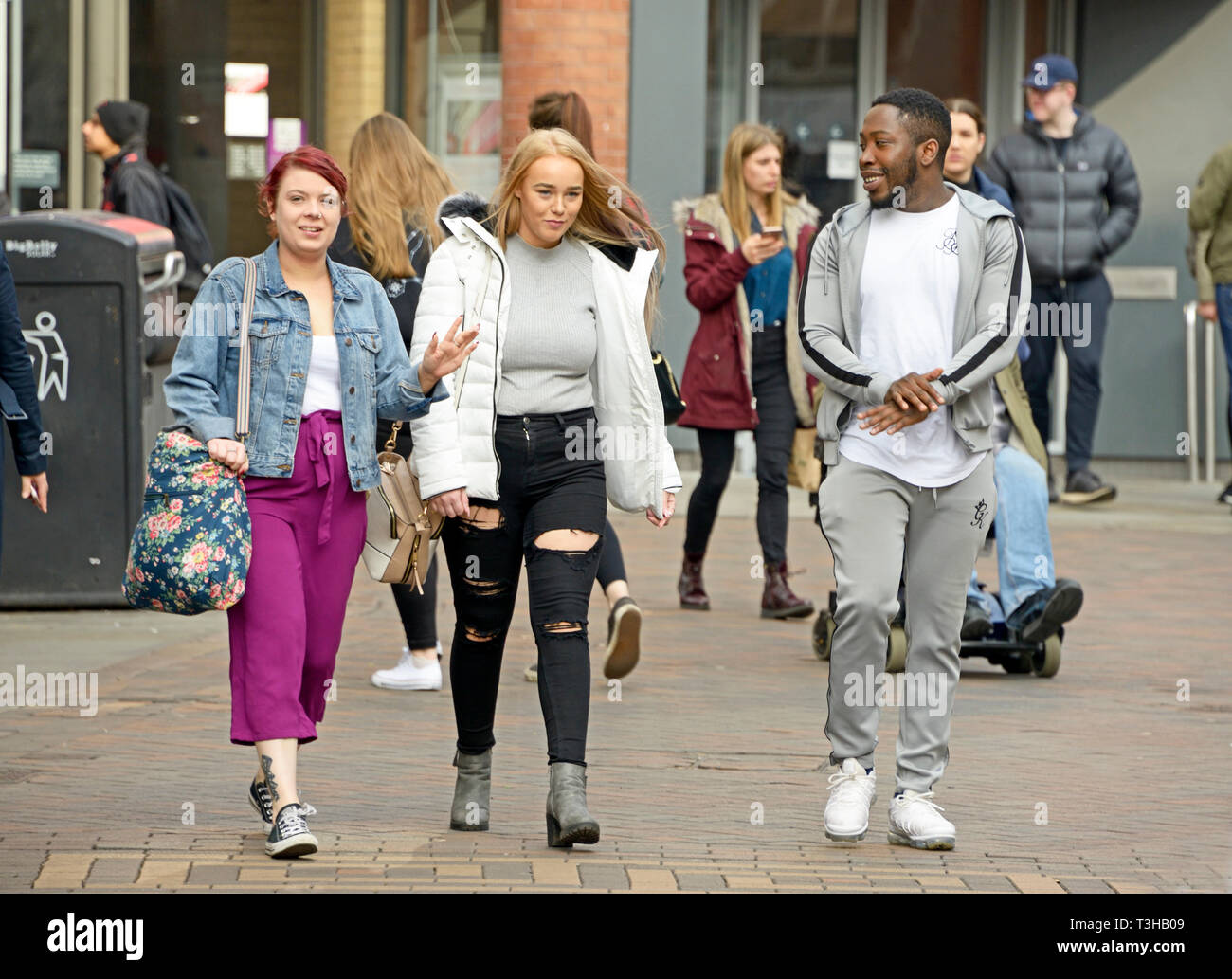 Black youth, walking with two white girls, talking. - Stock Image