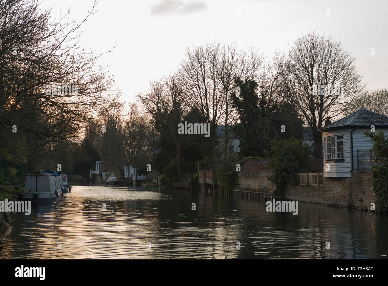 Sun setting on the Ware Lock. The lock on the River Lee Navigation. The huts/ gazebos (summerhouses) run along the bank of the River Lee. - Stock Image