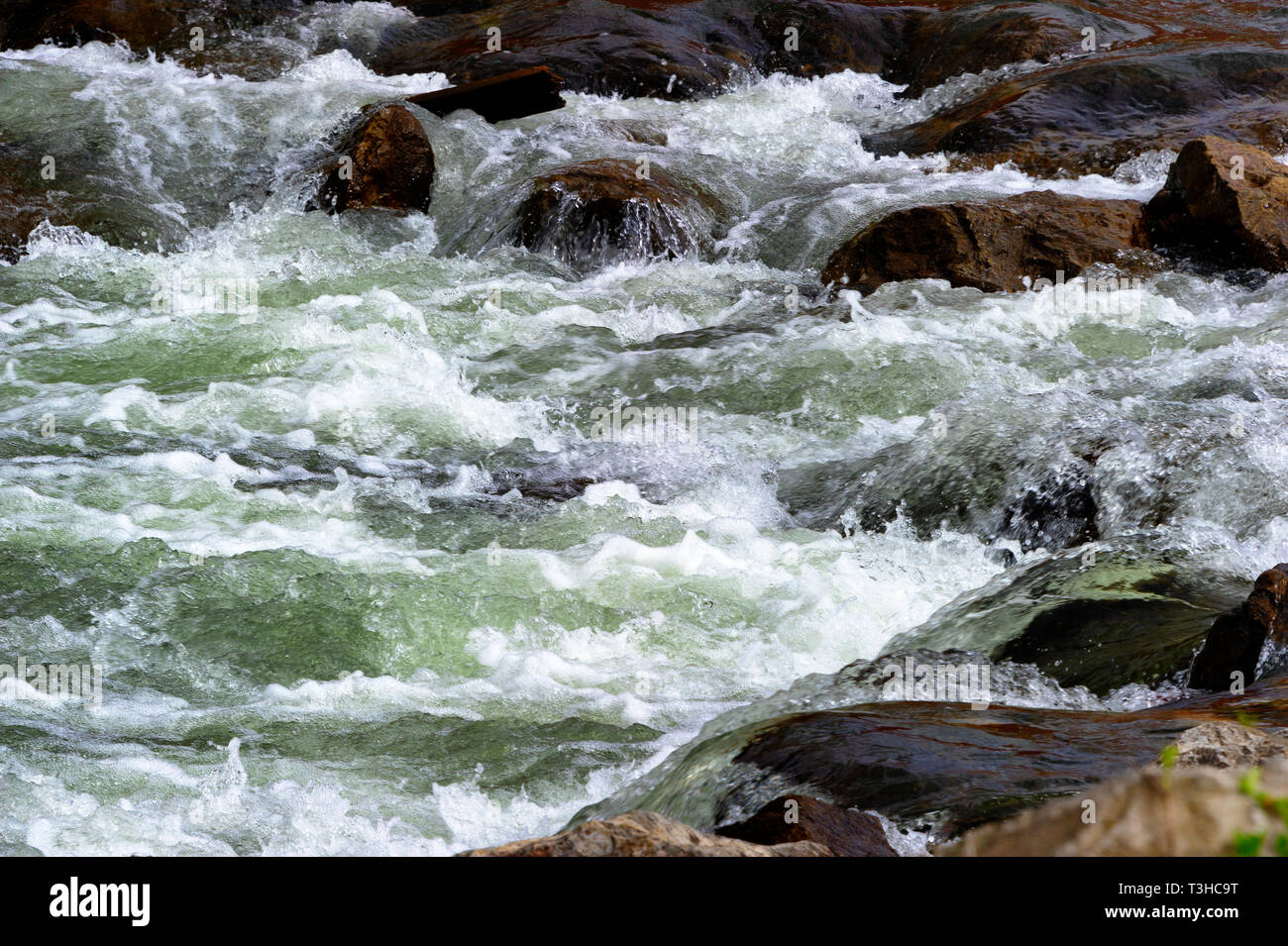 Cascading river water flows over rocks in the river creating rapids. - Stock Image