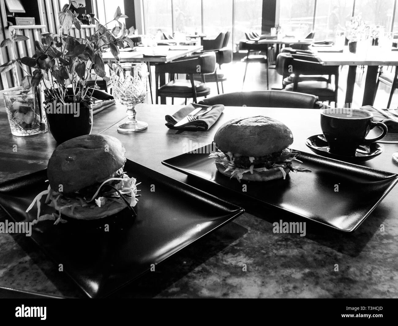 Tasty huge burgers in a restaurant cafe - Stock Image