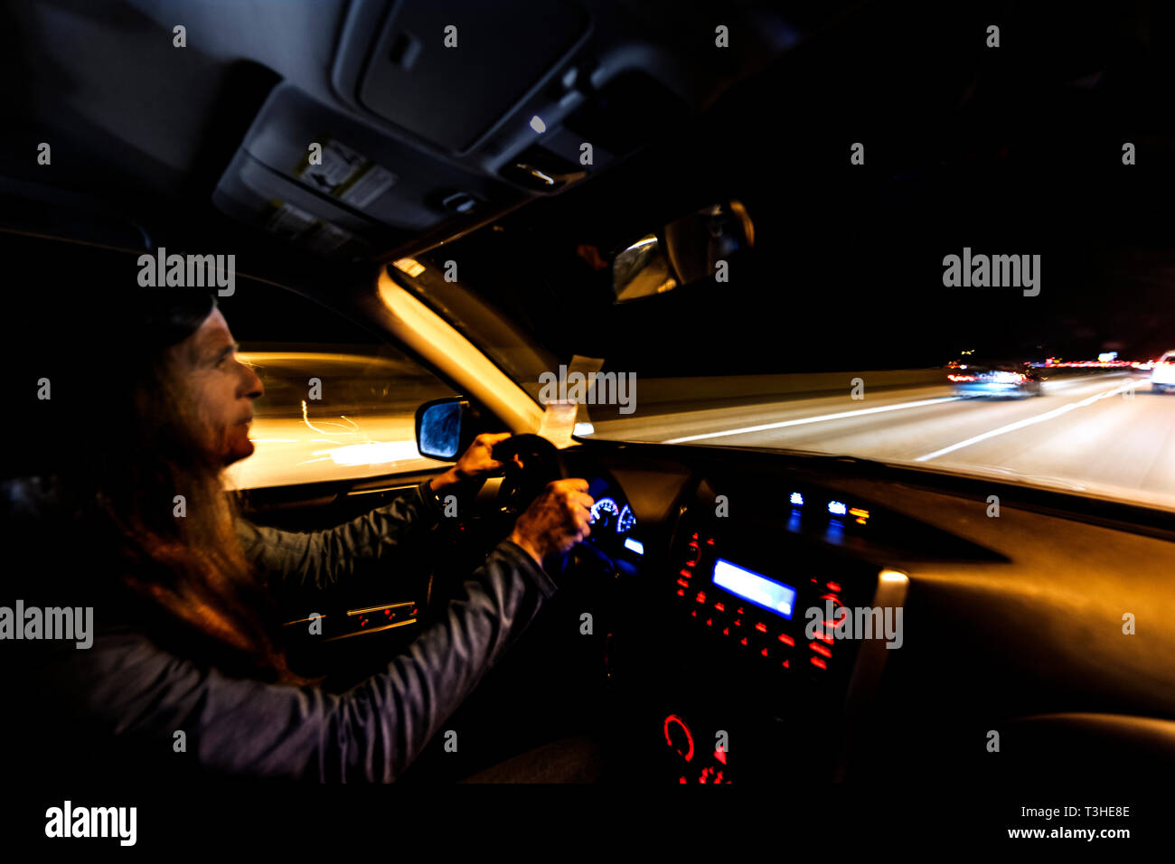 WA17076-00...WASHINGTON - Woman driving Interstate 5 at night near Seattle. (MR# S1) - Stock Image