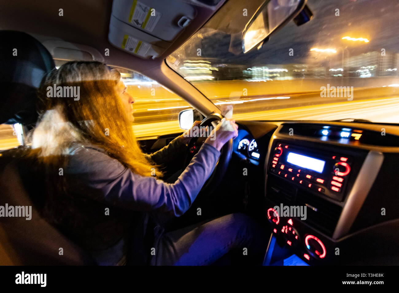 WA17077-00...WASHINGTON - Woman driving Interstate 5 at night near Seattle. (MR# S1) - Stock Image