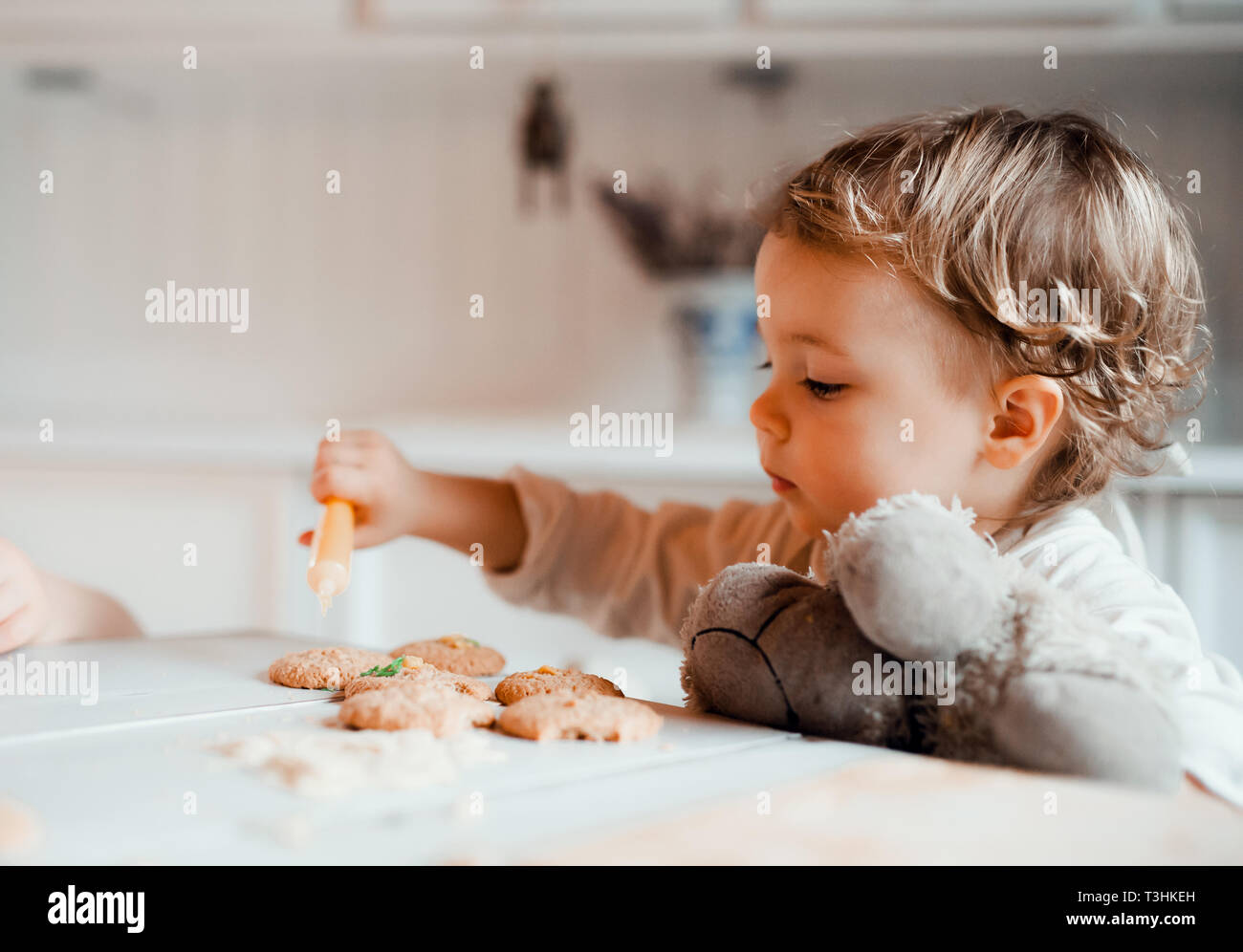 A small toddler girl sitting at the table, decorating cakes at home. - Stock Image