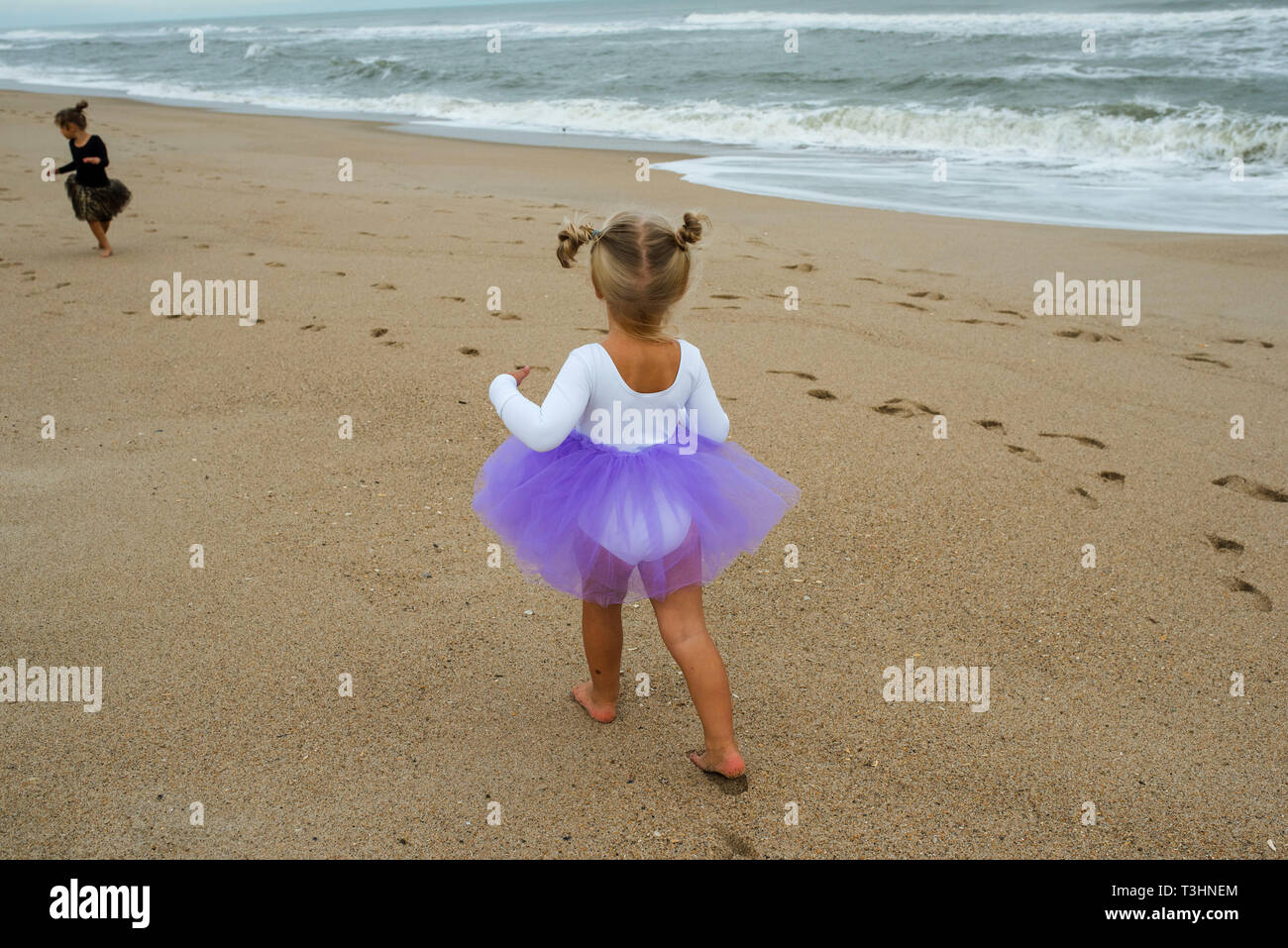 Two little girls running on the beach - Stock Image