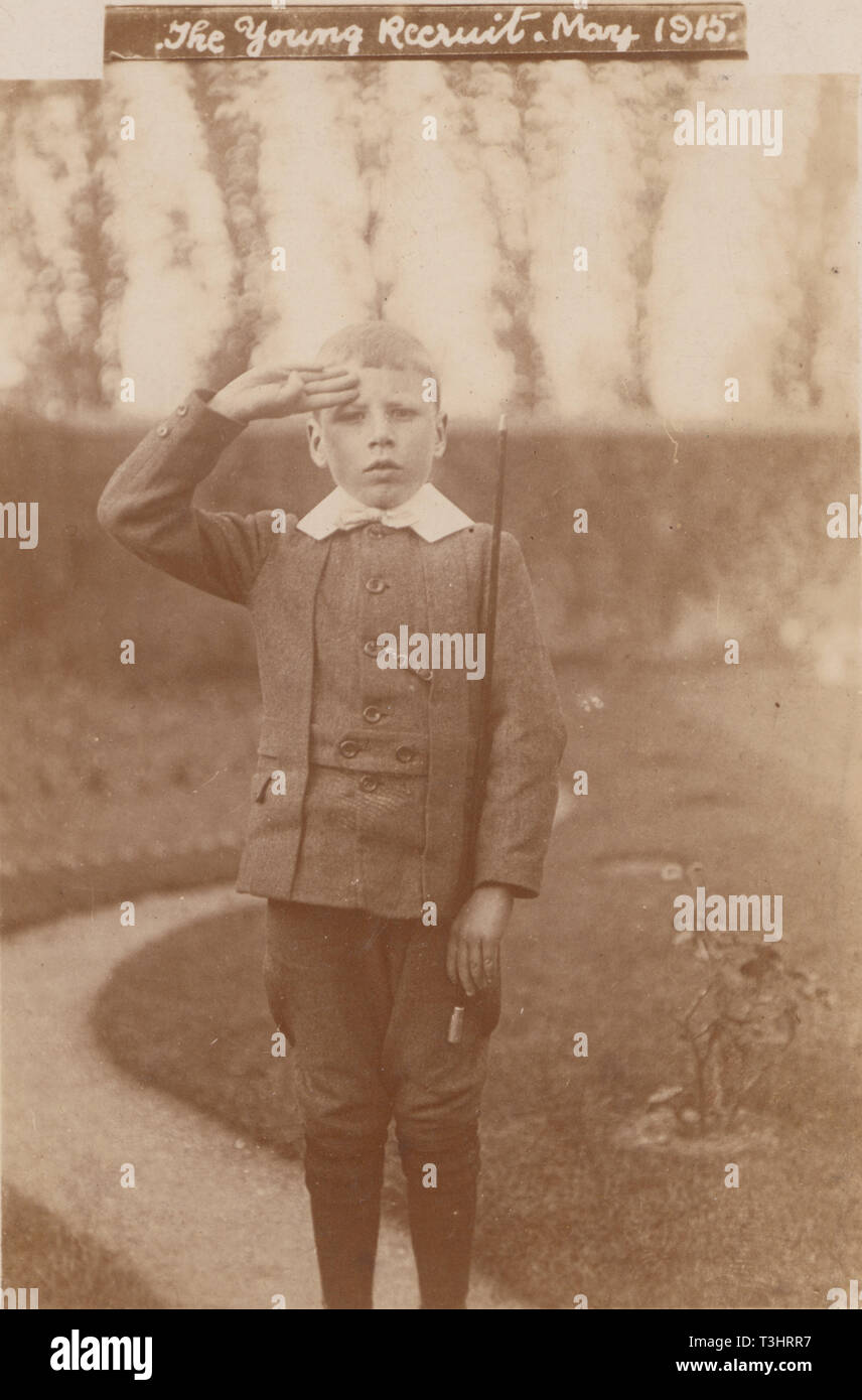 Vintage Photographic Postcard Showing a Young Boy Standing To Attention and Saluting at The Time of The First World War. 'The Young Recruit, May 1915' - Stock Image