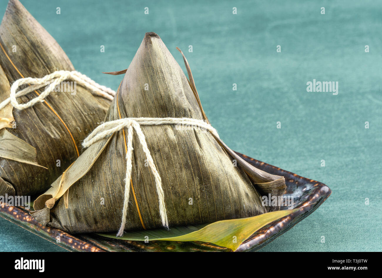 Close up, copy space, famous chinese food in dragon boat (duan wu) festival, steamed rice dumplings pyramidal shaped wrapped by bamboo leaves made by  Stock Photo