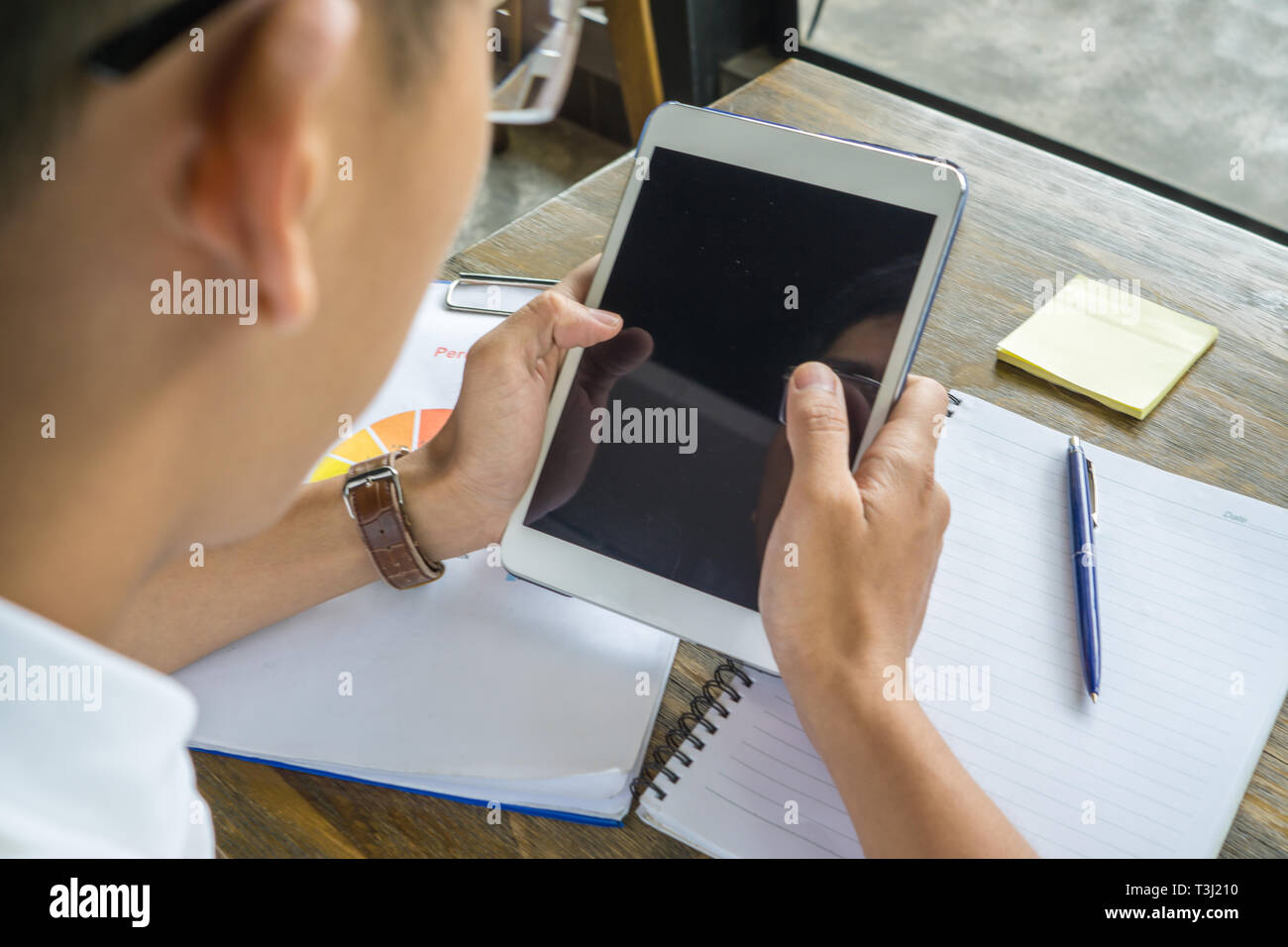 Close-up of human hand tapping on tablet surface - Stock Image