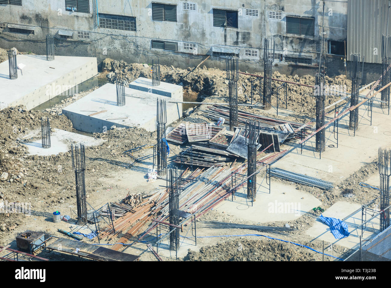 Construction Industry, Concrete building construction site. Concrete piles driven into the substructure ground at foundation pit. Industrial Business, - Stock Image