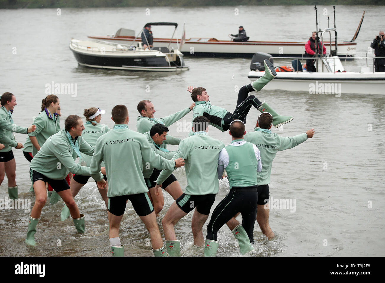 Cambridge cox Matthew Holland is thrown in the water after winning the during the Men's Boat Race on the River Thames, London. Stock Photo