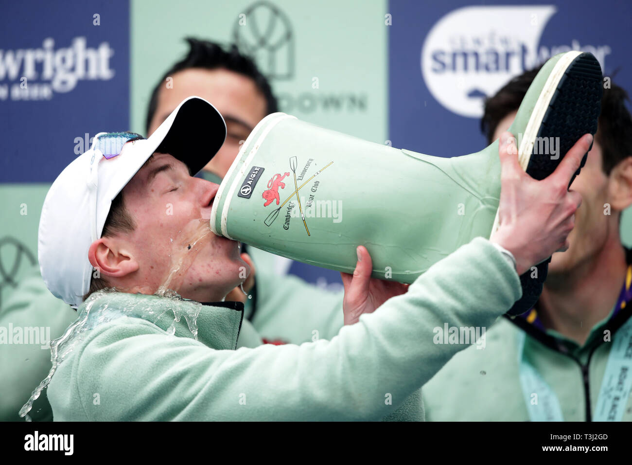 Cambridge cox Matthew Holland drinks champagne from a welly after winning the Men's Boat Race on the River Thames, London. Stock Photo
