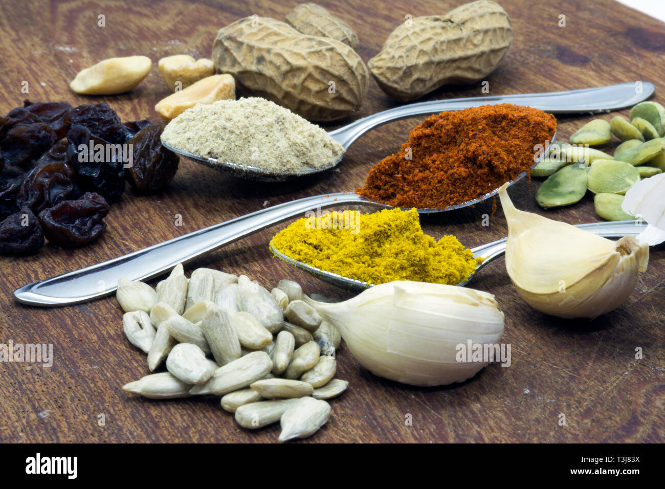 seasonings on some spoons, pepper, paprika and turmeric, garlic and pumpkin seeds and sunflower on a wooden board with autumn colors Stock Photo
