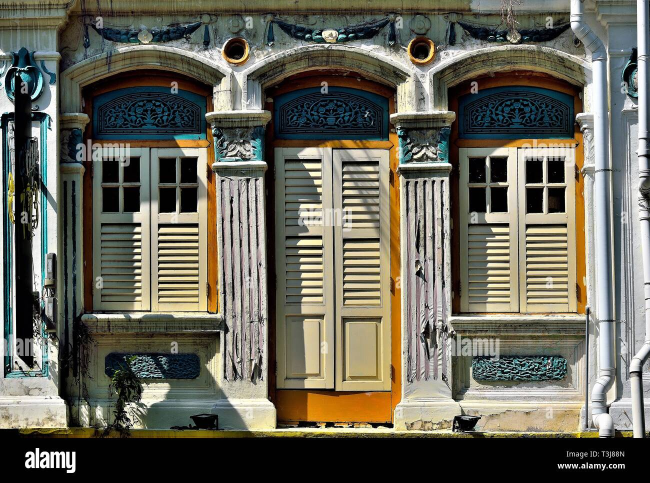 Straits Chinese or Peranakan Singapore shop house with ornate exterior, antique louvered shutters and arched windows in historic Little India Stock Photo