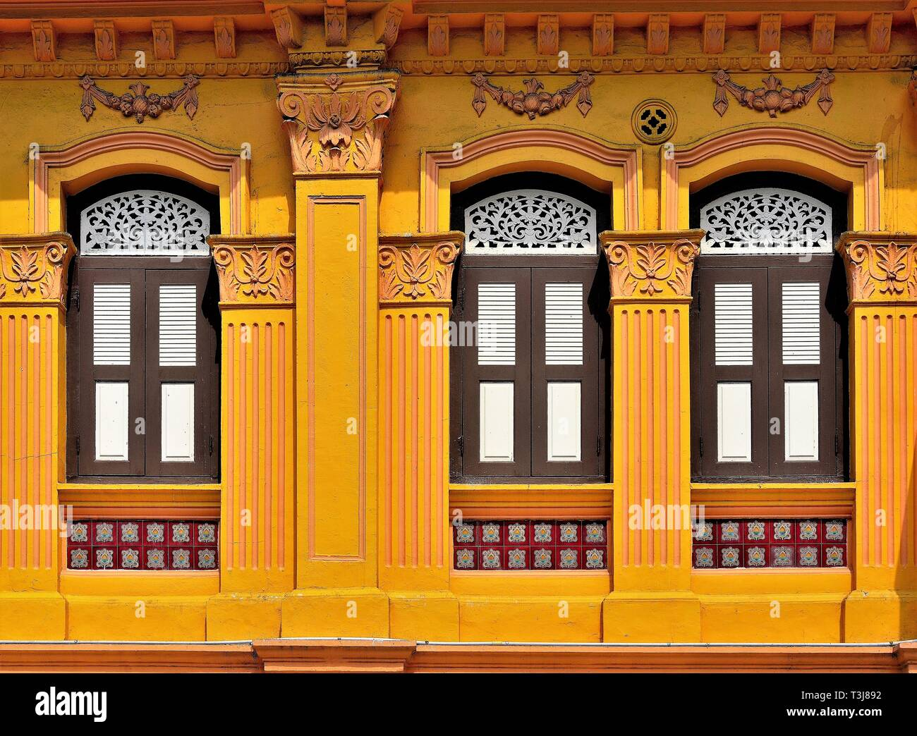 Traditional Straits Chinese or Peranakan vintage shop house with antique wooden shutters and orange exterior in Little India Singapore - Stock Image