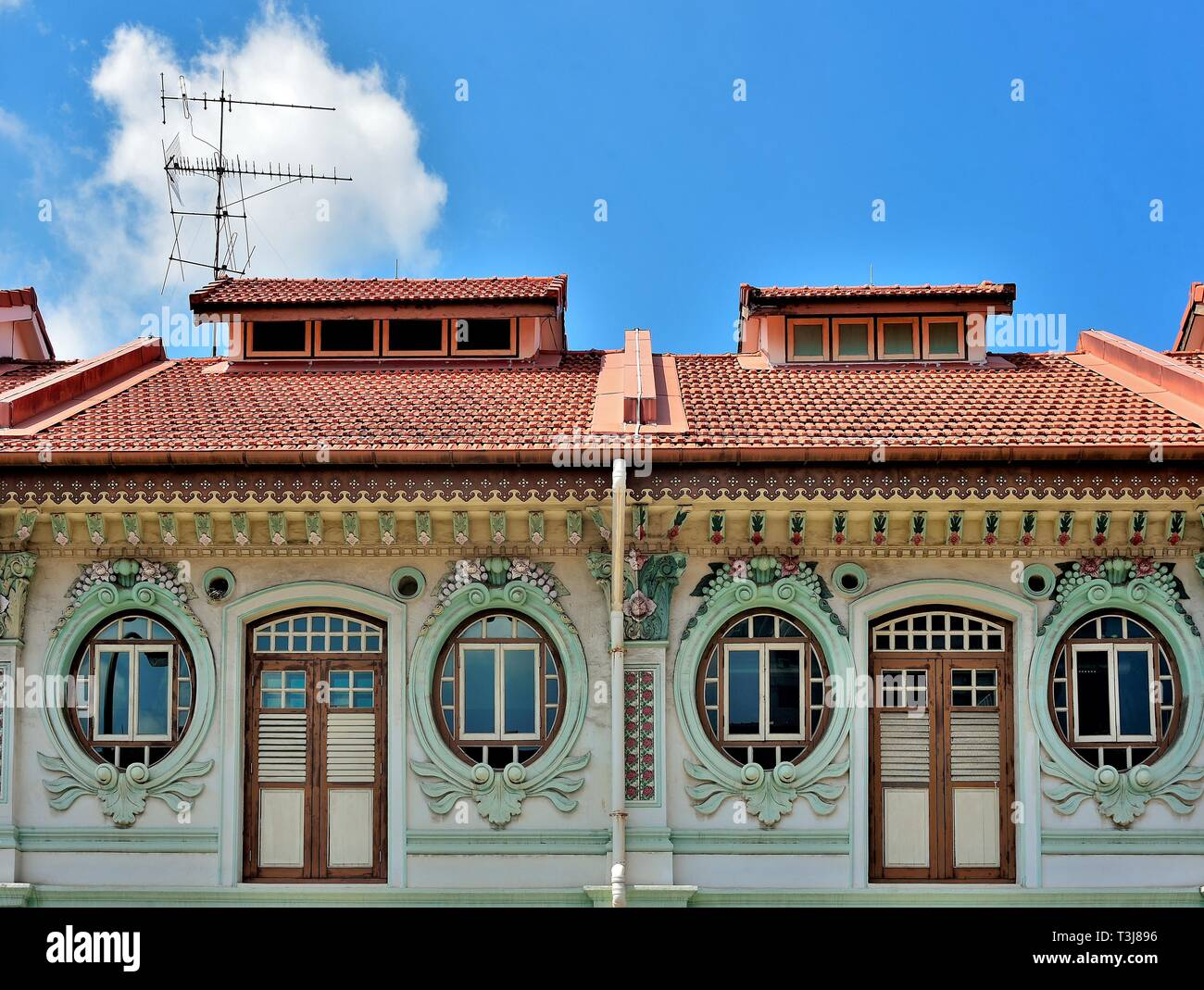 Front view of traditional Peranakan or Straits Chinese Singapore shop house exterior with unique oval windows  in historic Little India Stock Photo