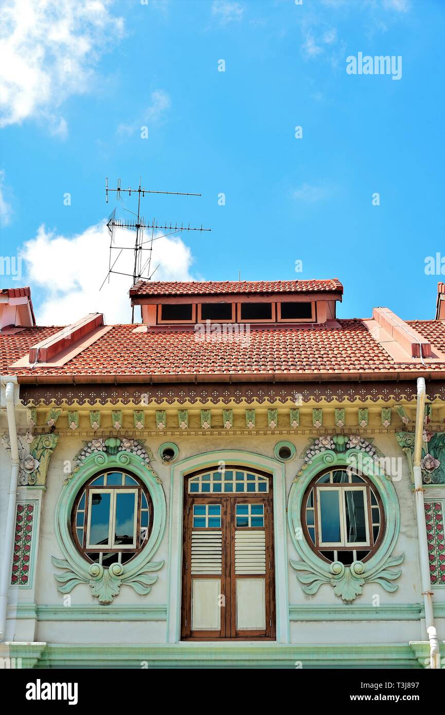 Front view of traditional Peranakan or Straits Chinese Singapore shop house exterior with unique oval windows  in historic Little India - Stock Image