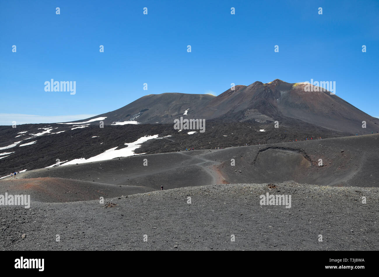 Etna volcano in Sicily, partly covered with snow, mediterranean coast, footpaths near the craters, blue sky, sunny, summer, adventure, experience - Stock Image