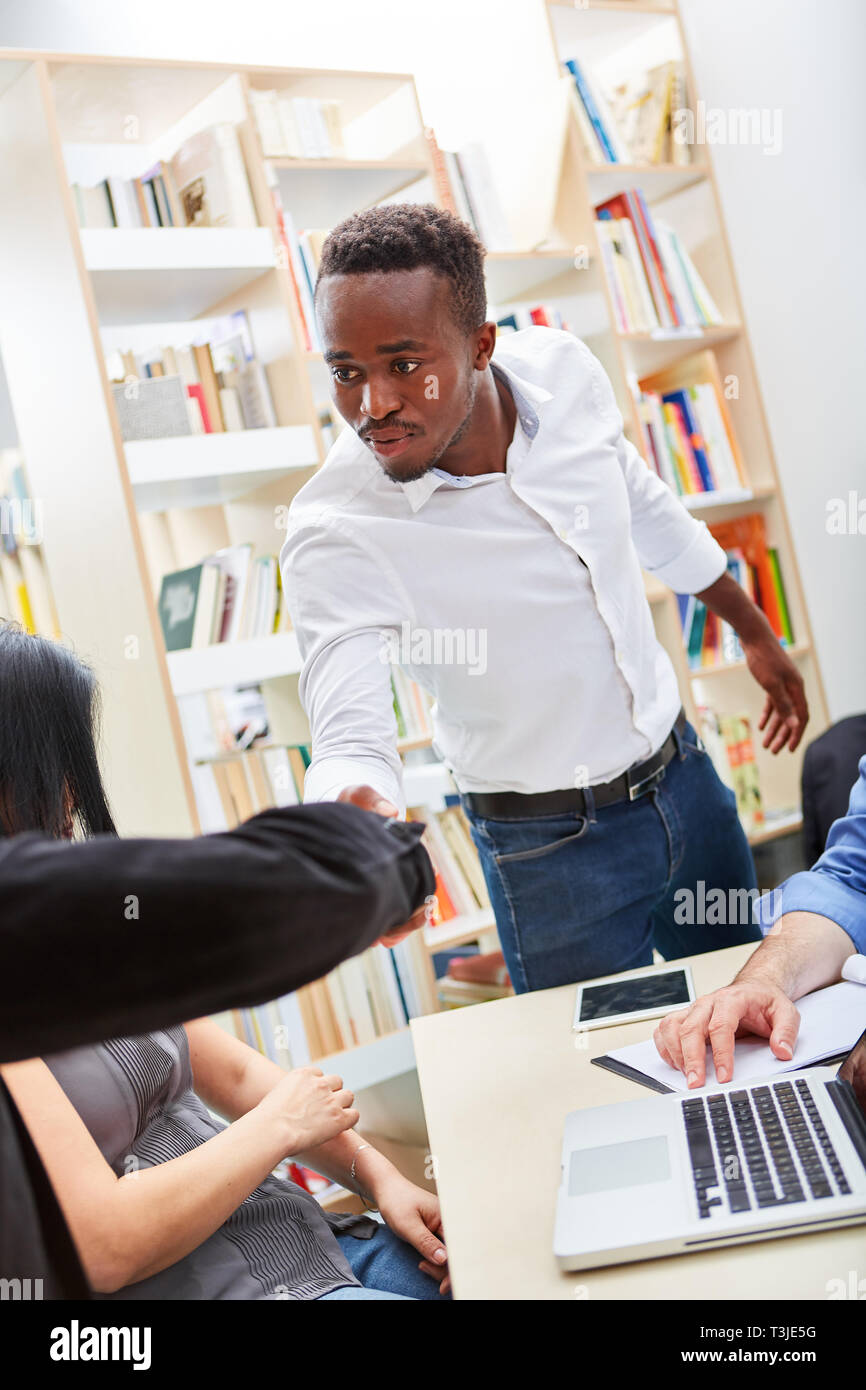 Young African student or immigrant shakes hands with a fellow student - Stock Image