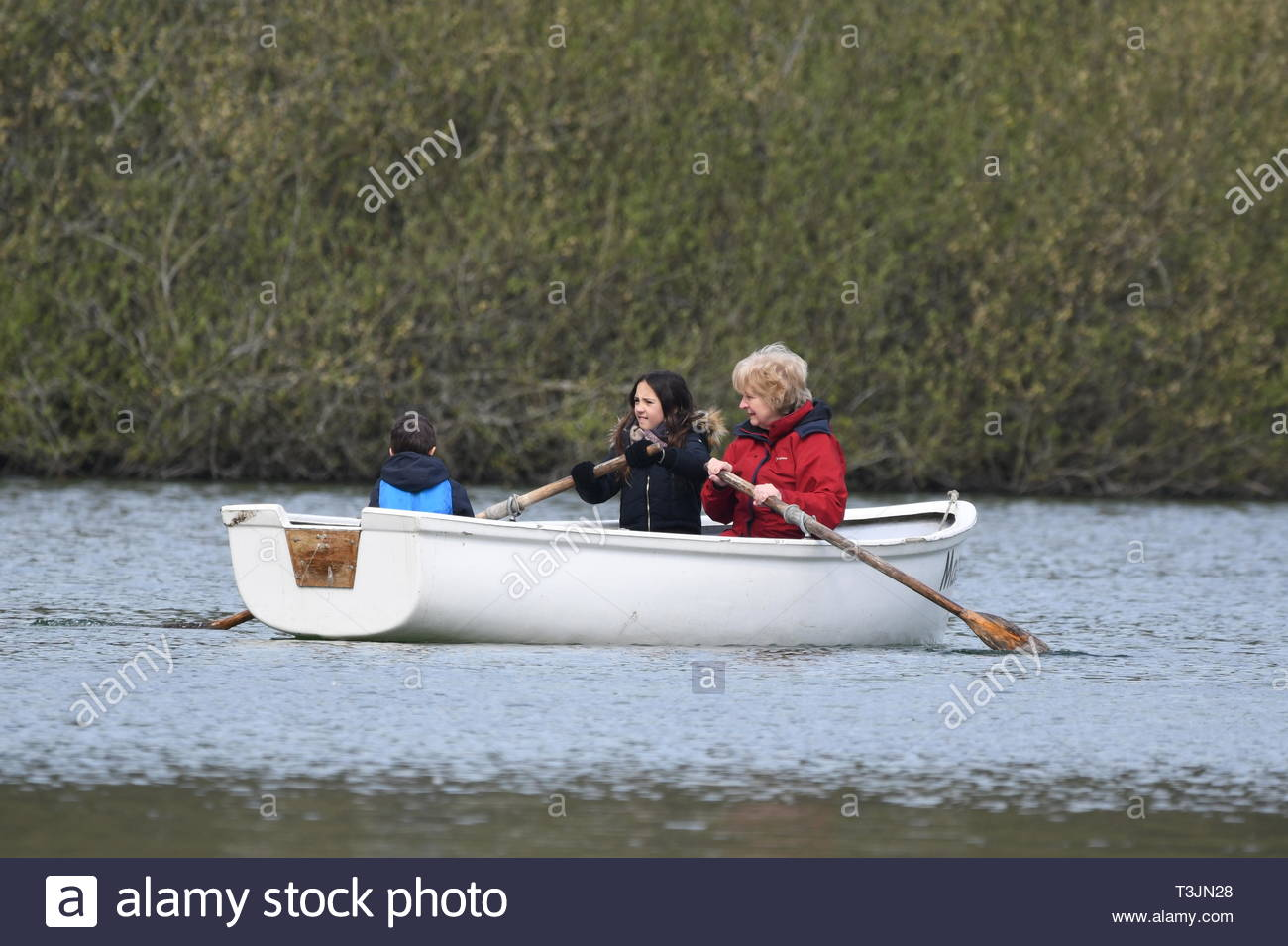 Arundel, West Sussex, UK. Wednesday 10th April 2019. People in a rowing boat on Swanbourne Lake on a partly cloudy but bright and cool morning in Arundel, near the South Coast. Credit: Geoff Smith/Alamy Live News - Stock Image