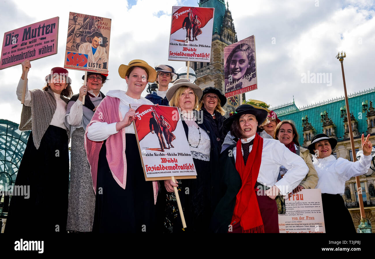 Hamburg, Germany. 10th Apr, 2019. Female members of the Hamburg SPD Parliamentary Group stand in historical costumes in front of the town hall. With this campaign entitled '100 years of women's suffrage: gender equality remains an obligation for Hamburg's democracy and society', the participants warned that equality is still not a matter of course today. Credit: Axel Heimken/dpa/Alamy Live News - Stock Image