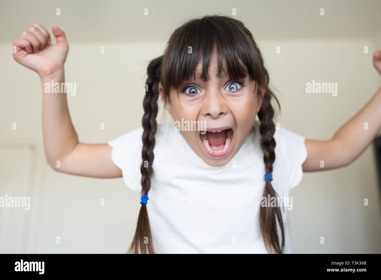 Angry girl is screaming towards the camera. She is mad. - Stock Image