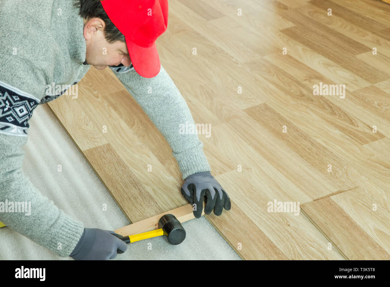 Man laying laminate flooring in construction concept - Stock Image