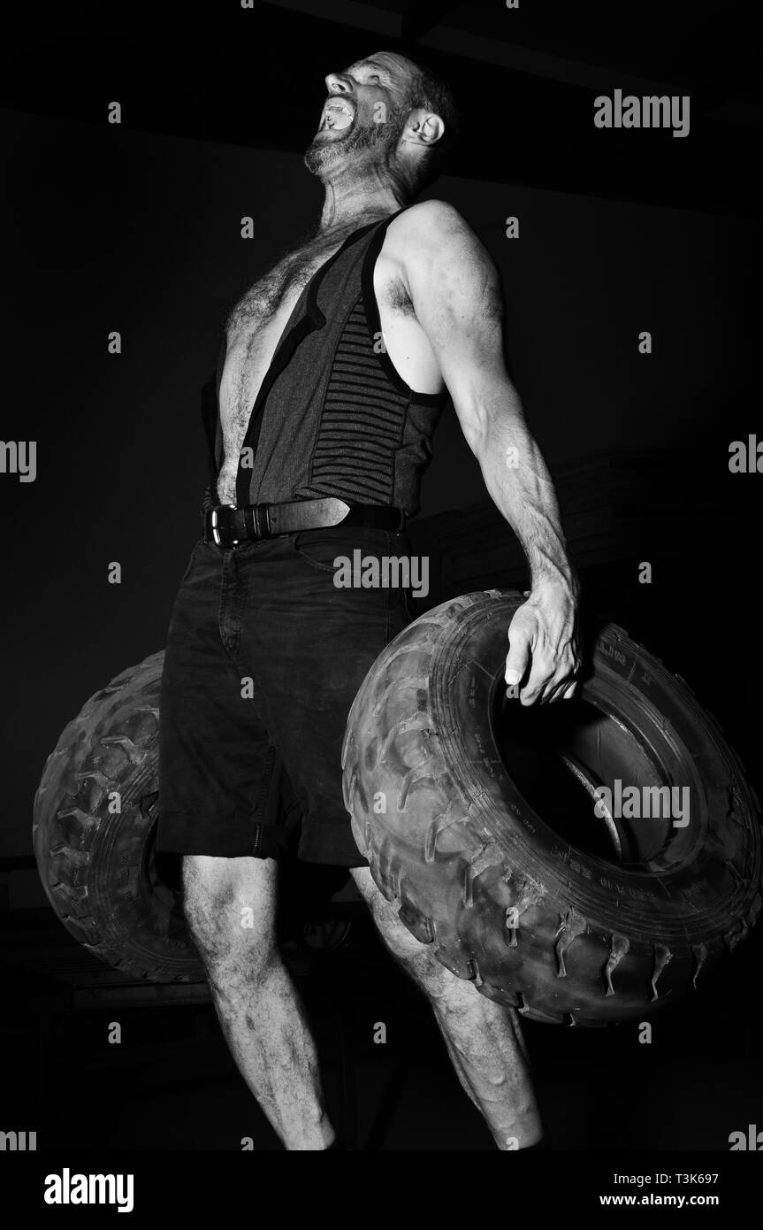 Powerful man makes bodybuilding with old car tires - Stock Image