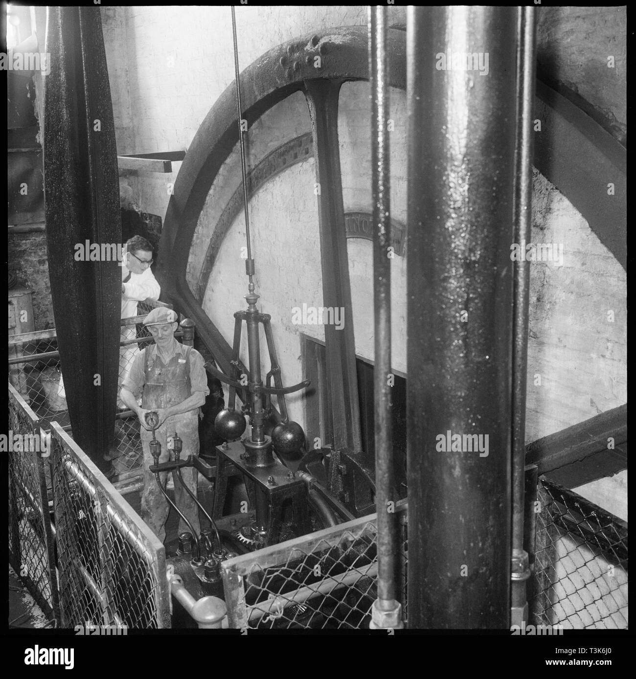 Etruscan Bone and Flint Mill, Lower Bedford Street, Etruria, Hanley, Stoke-on-Trent, 1965-1968. The mill engineer adding oil to 'Princess', the beam engine at Jesse Shirley's Bone and Flint Mill (Etruscan Mills). The mill was constructed by Shirley in 1856. It was used to crush flint and bone which was added to clay to provide the raw material for the production of earthenware goods. It is now home to the Etruria Industrial Museum. - Stock Image