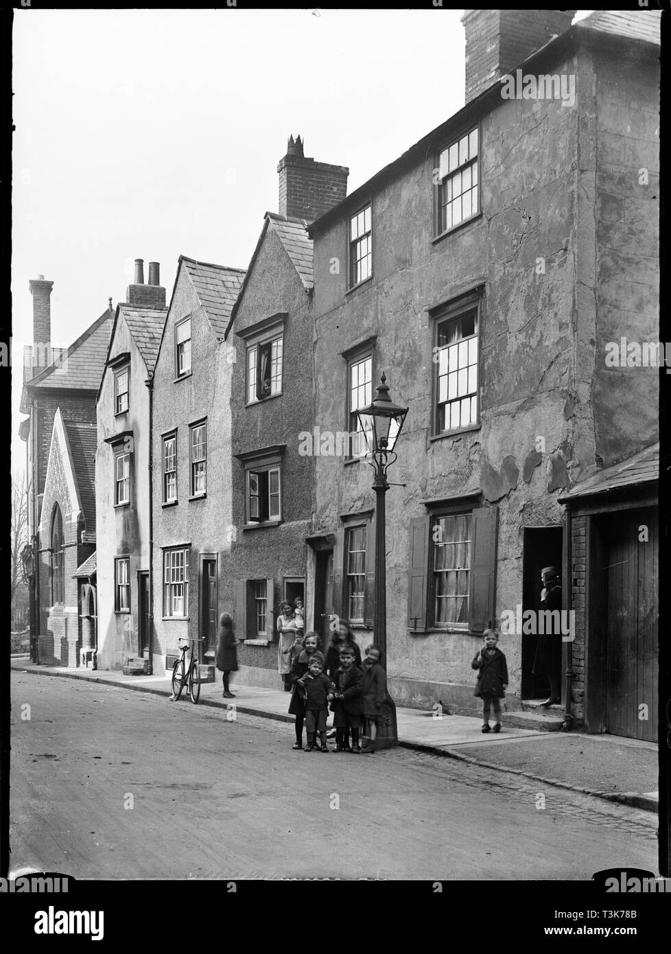 Beef Lane, Oxford, Oxfordshire, 1928. A view of 17th and 18th century houses on the north side of Beef Lane, showing the fronts of numbers 4-8 from the south-west, with children in the foreground standing beside a lamp post. This row of houses has subsequently been demolished. - Stock Image
