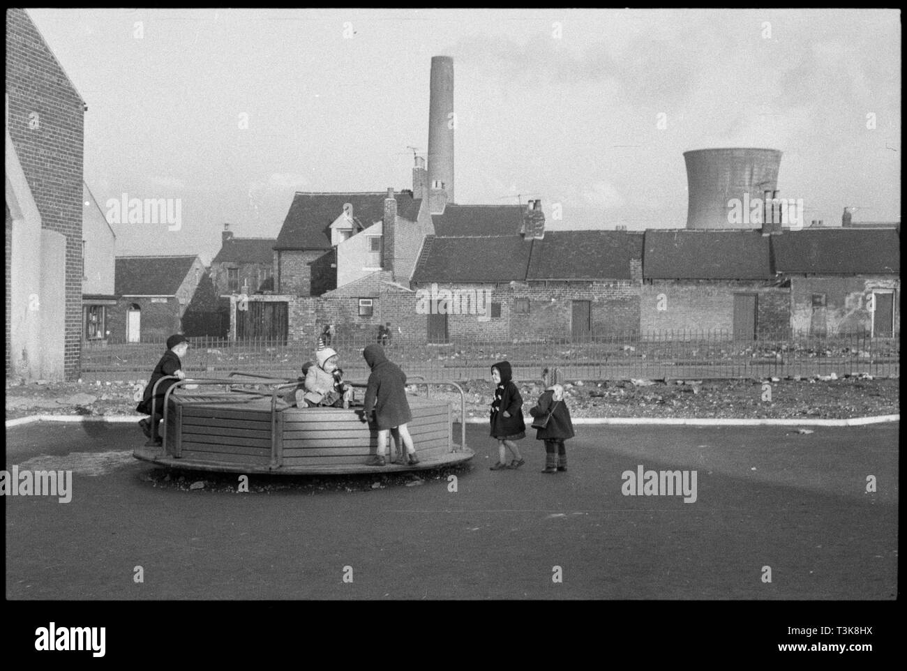 "Children's playground, Lansdowne Street, Millfield, Sunderland, 1961. Children playing on a roundabout in the Landsdowne Street playground with the rear of houses on Millburn Street in the background. This is one of a group of photographs associated with the Pyrex factory (Wear Flint Glass Works, manufacturers of Pyrex in the UK) for which the original archive enclosure gives the following information: ""Jan 1961; Outside the Factory, Streets and Children"". - Stock Image"