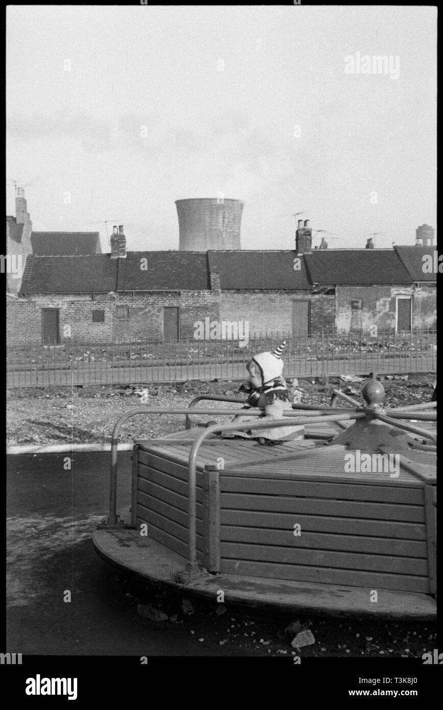 "Children's playground, Lansdowne Street, Millfield, Sunderland, 1961. A young child playing on a roundabout in the Landsdowne Street playground with the rear of houses on Millburn Street in the background. This is one of a group of photographs associated with the Pyrex factory (Wear Flint Glass Works, manufacturers of Pyrex in the UK) for which the original archive enclosure gives the following information: ""Jan 1961; Outside the Factory, Streets and Children"". - Stock Image"