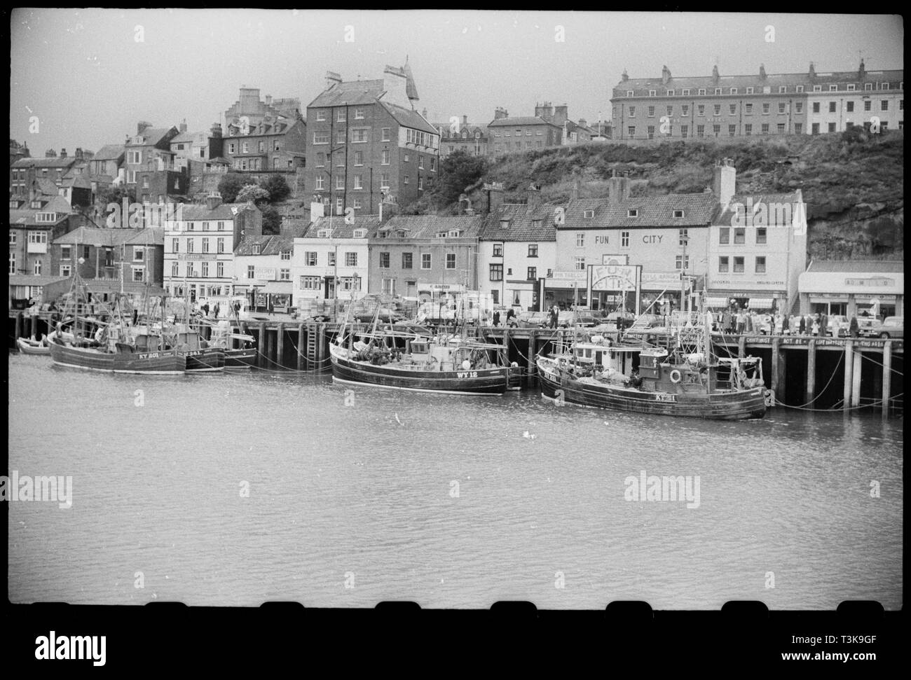 Whitby harbour, North Yorkshire, c1955-c1980. A general view of buildings along the west side of the harbour, showing two and three storey shops along the pier and houses in the background, higher up the cliff. The building on the right side are part of a group of 18th century buildings on the Cragg, and include three storey buildings with modern shop fronts on the ground floor, and some two storey buildings on the left, with attics. On the cliff-face is Streonshall, a 19th century house which utilises the cliff, with five storeys at the rear of the house, and two at the front, with an octagon - Stock Image