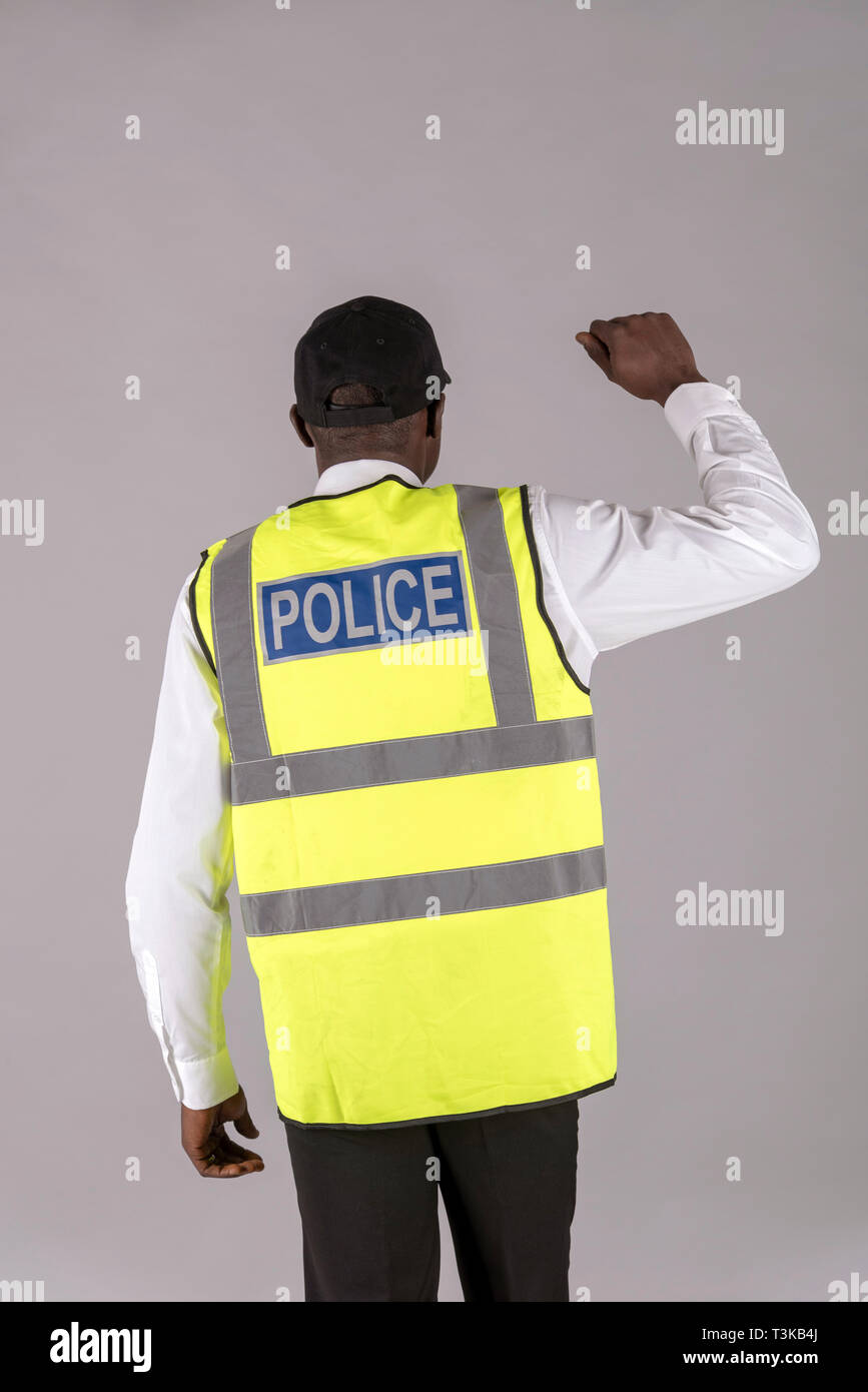 Salisbury, Wiltshire, UK, April 2019. Rear view of a police officer in reflective jacket and right arm raised. - Stock Image