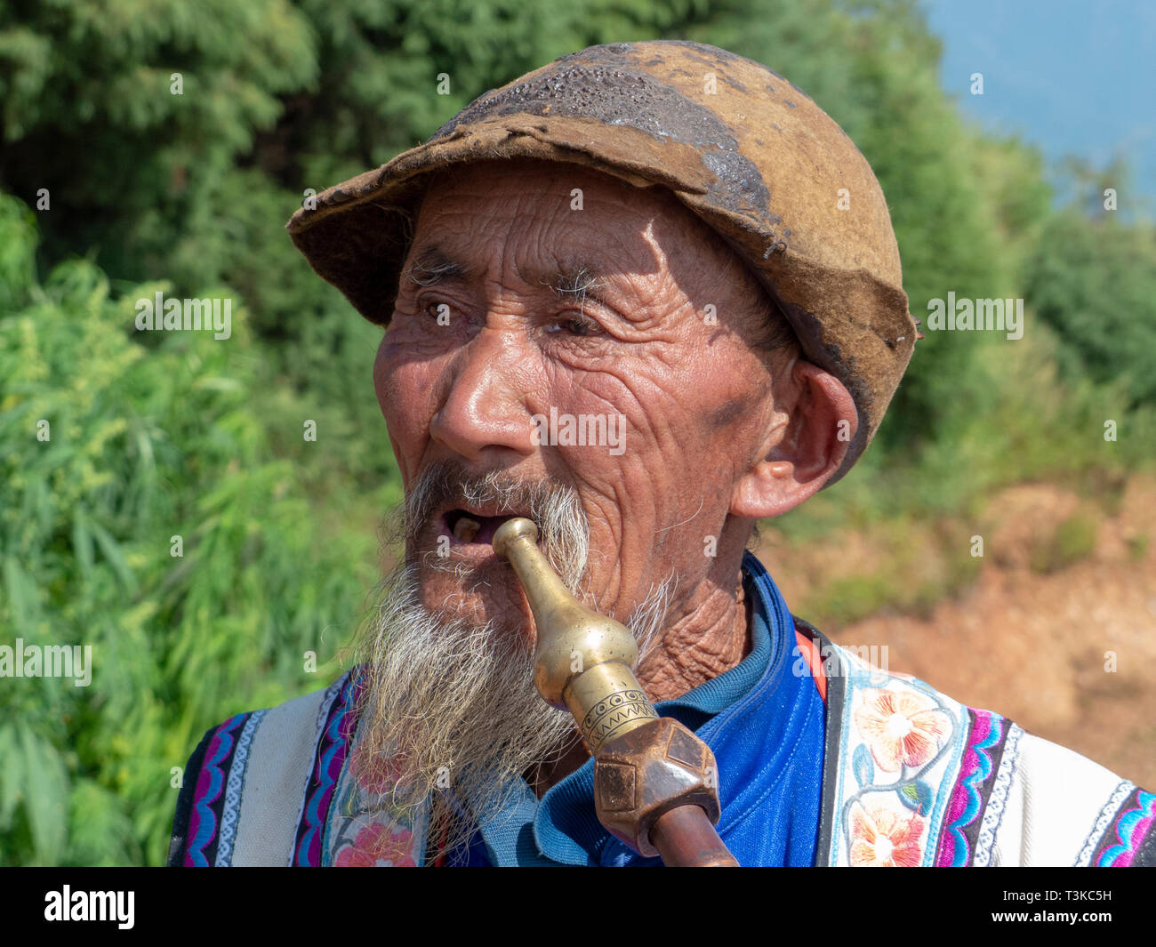 94e827349 Local Yi mature man smoking a pipe at a small village in the mountains in  the
