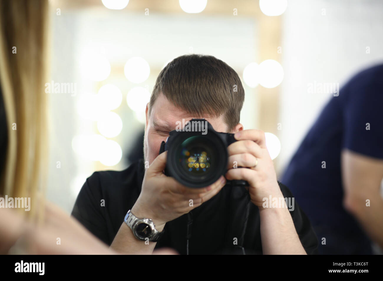 A male photographer holds camera in - Stock Image