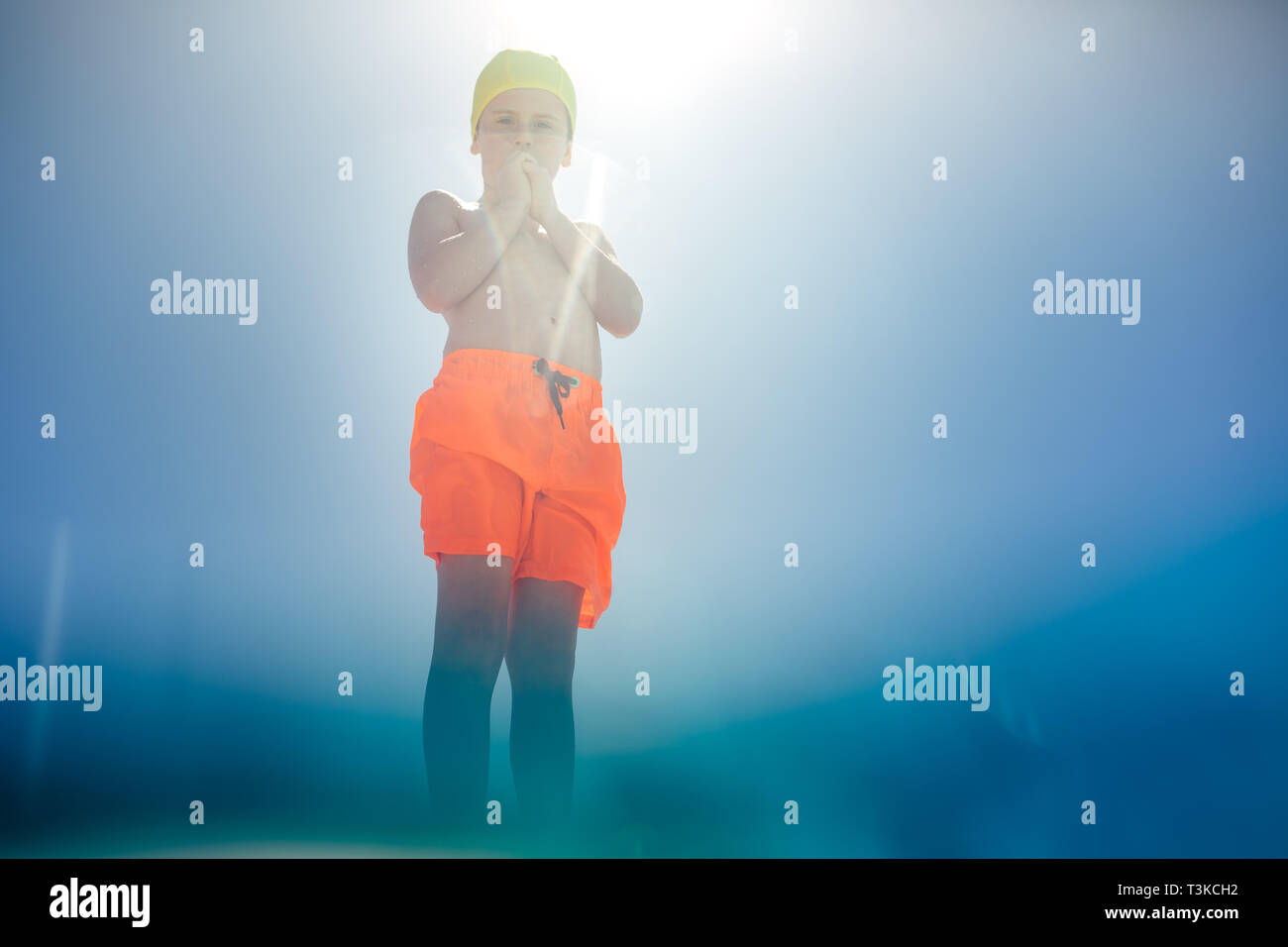 Low angle view of boy in swim trunks standing at the edge of the pool on sunny day. Boy in swimming costume seen from the pool. - Stock Image