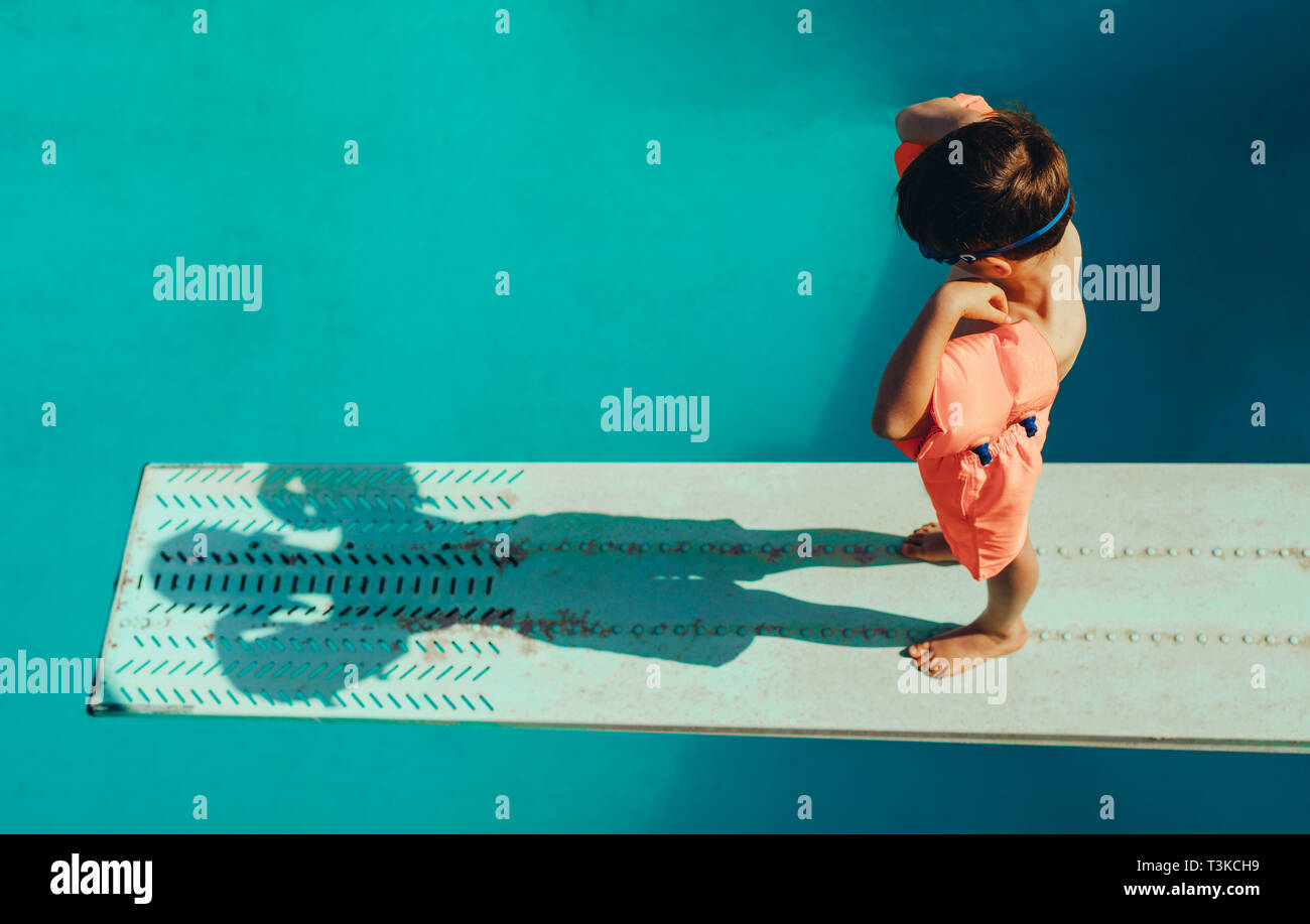 High angle shot of boy with sleeves floats on diving board preparing for dive in the pool. Boy standing on spring board at the swimming pool. Stock Photo