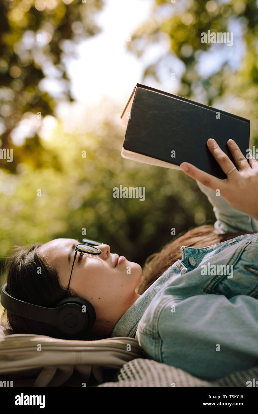 Close up of a young woman lying on ground and reading a book wearing headphones. Woman in a relaxed mood reading a book lying outdoors while listening Stock Photo