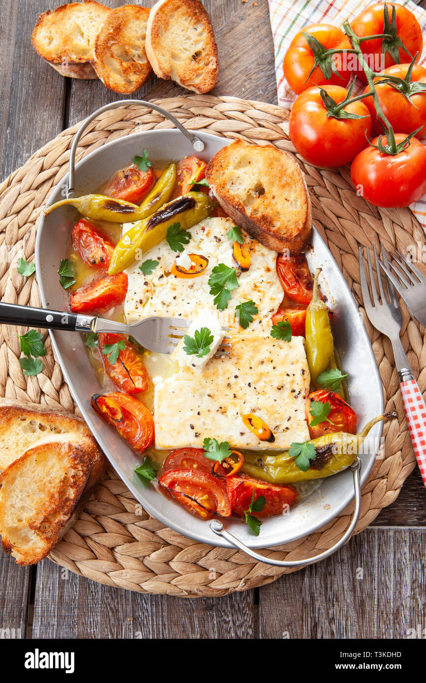 Gratinated feta cheese with tomatoes and chillis - Stock Image