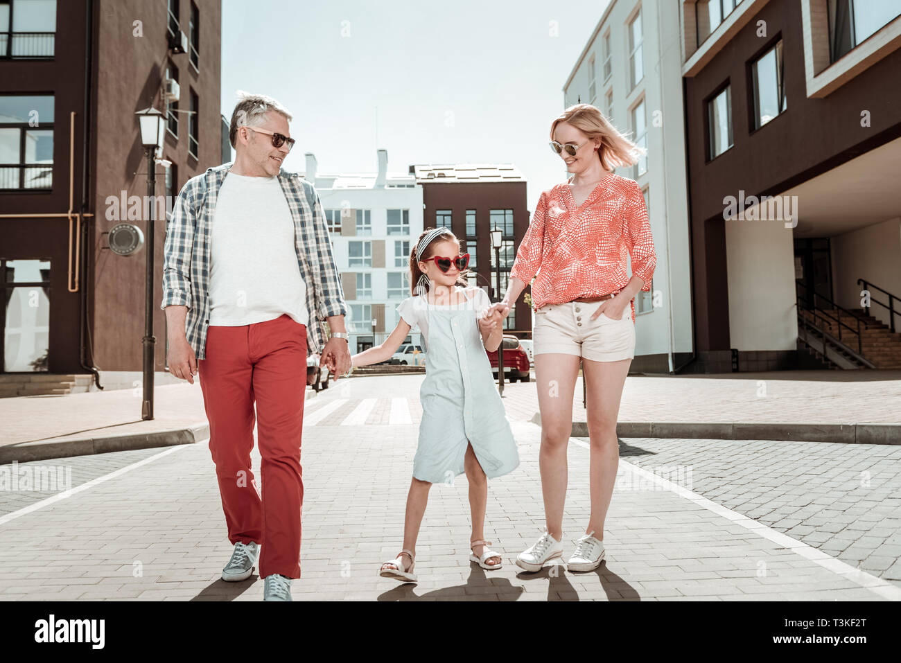 Positive cute girl holding her parents hands - Stock Image