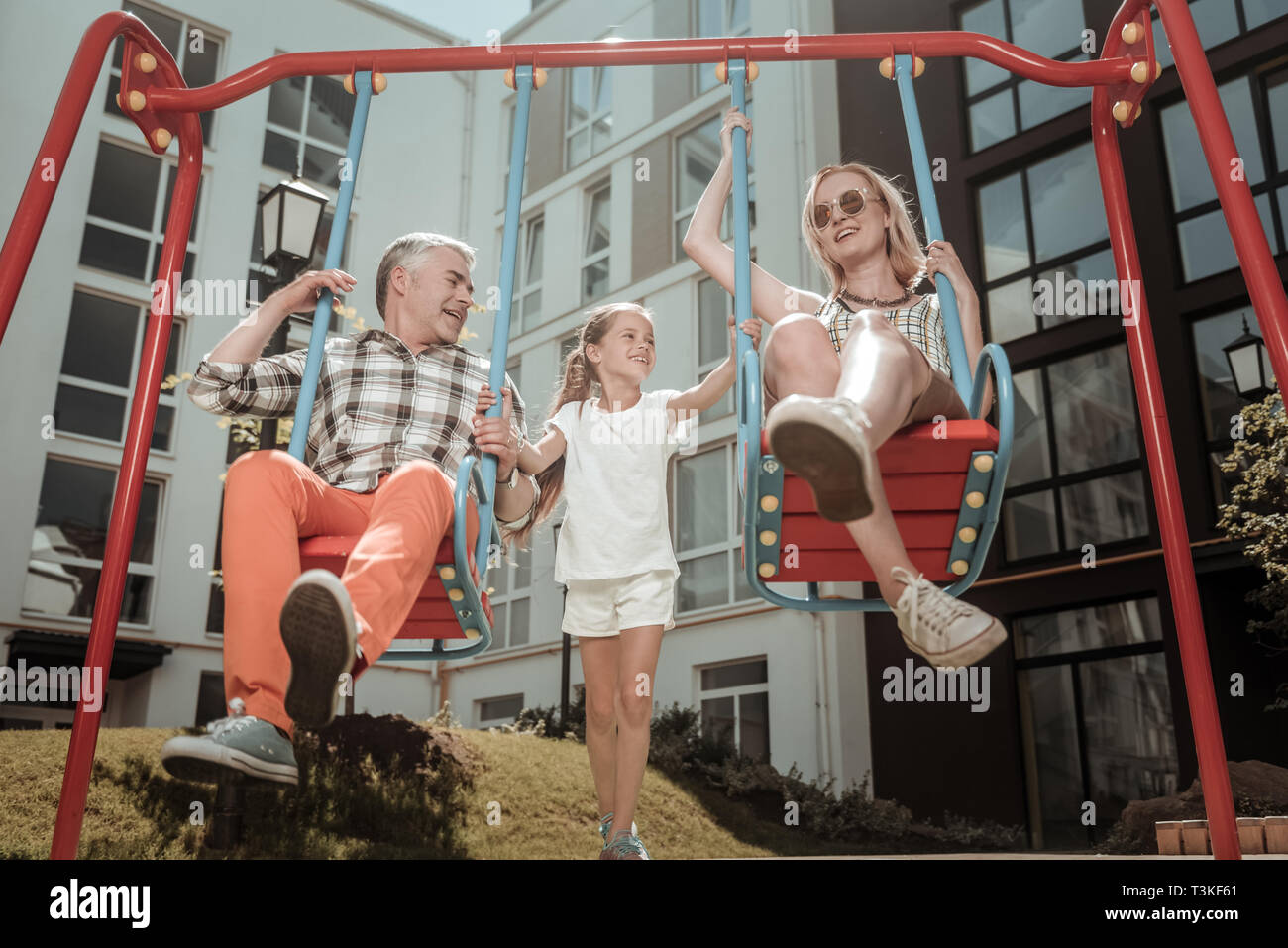 Happy delighted parents sitting on the swings - Stock Image