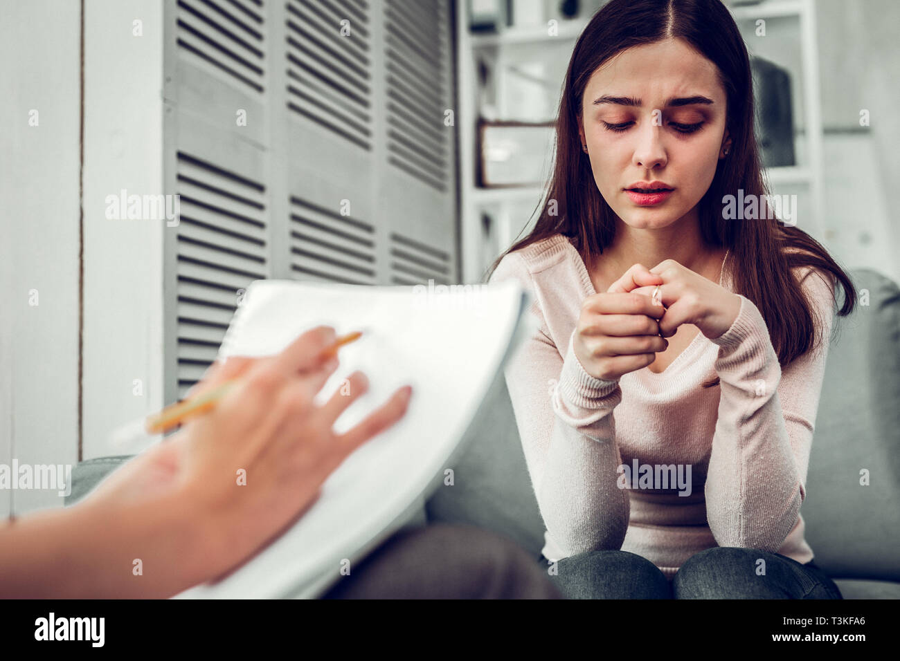 Young woman feeling stressed sharing personal feelings with therapist - Stock Image