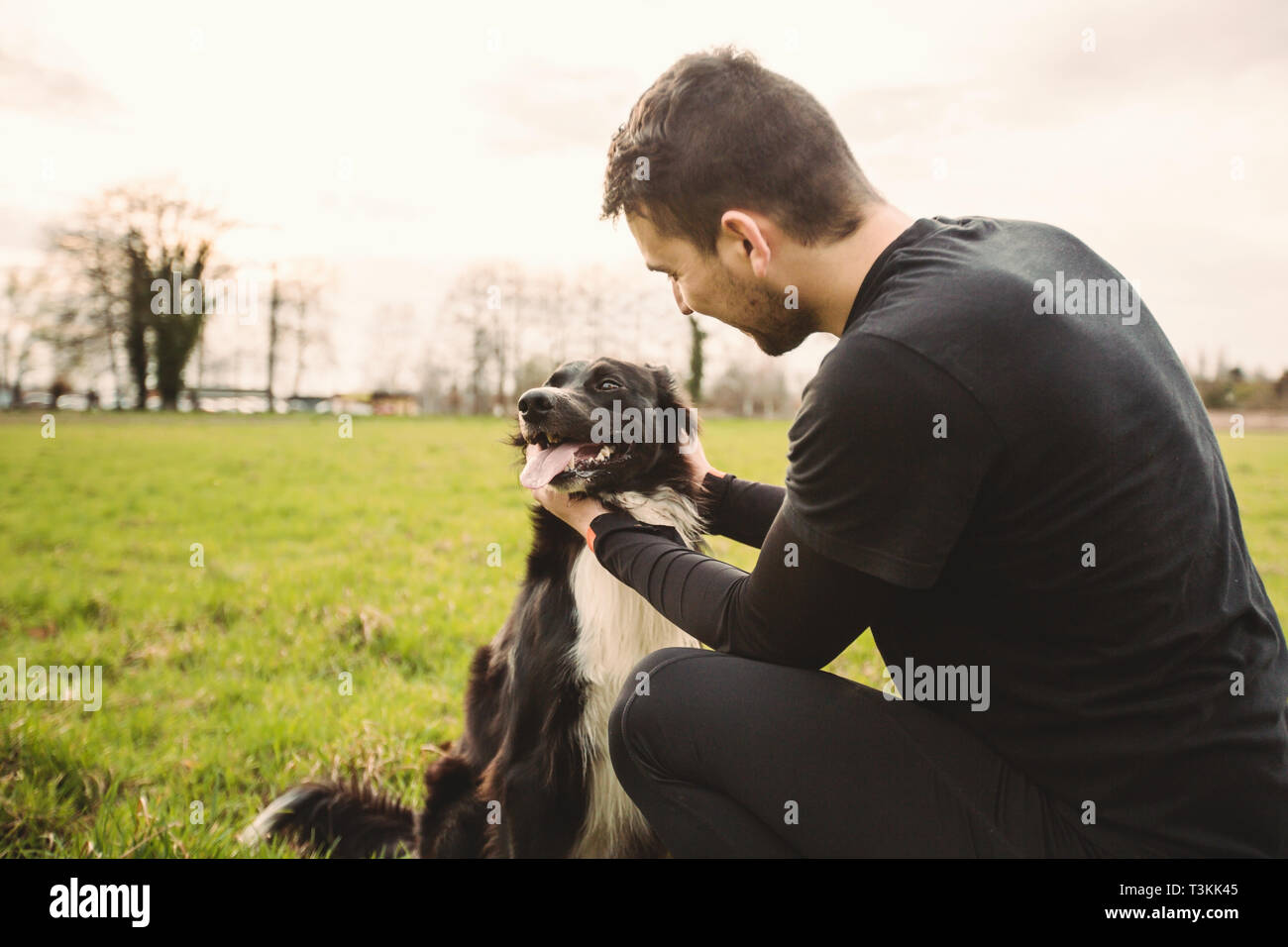 Man dog playing outdoor in the park. Young owner hugs his pet. Friendship between owner and dog. Animal love concept. Stock Photo