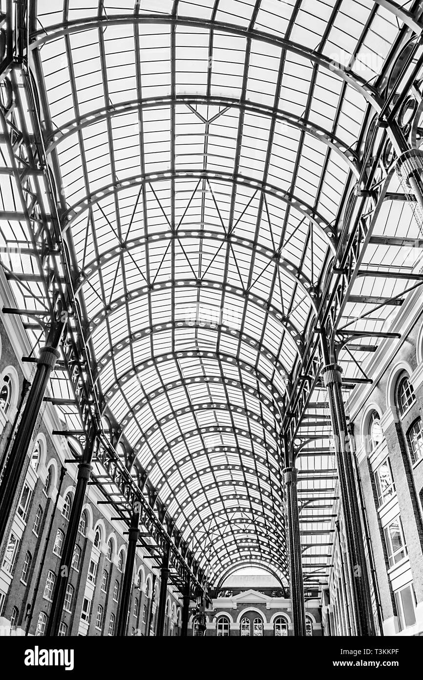 A black and white view of the curving glass ceiling of London Galleria - Stock Image