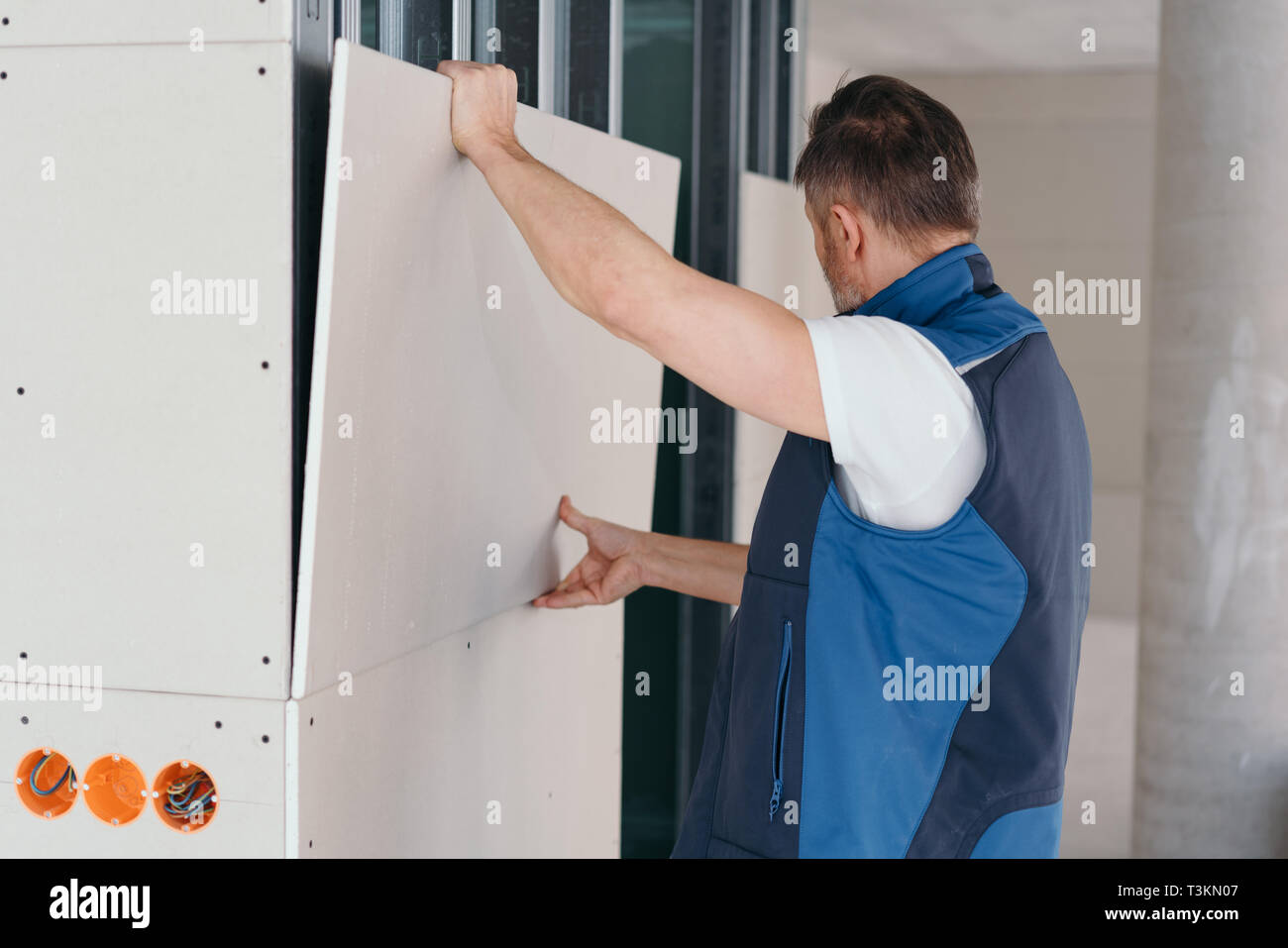 Builder fitting white wood cladding in a new build house with open electrical sockets visible below Stock Photo
