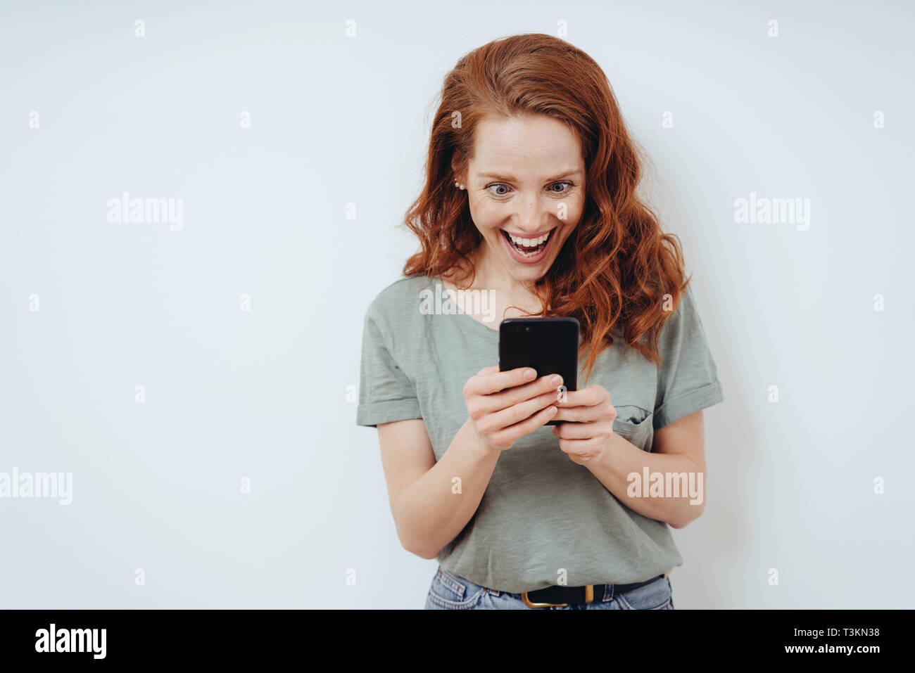 Gleeful young woman receiving good news on her mobile phone reading the message with a beaming smile and look of amazement - Stock Image