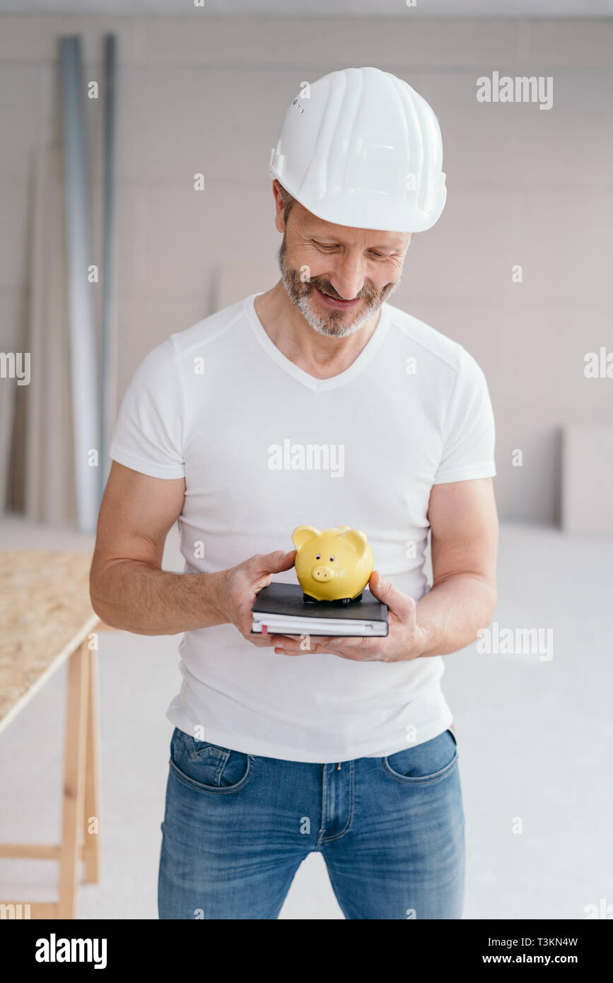 Builder smiling with satisfaction at a piggy bank balanced on top of his order book in his hands in a new build house in a concept of success and savi - Stock Image