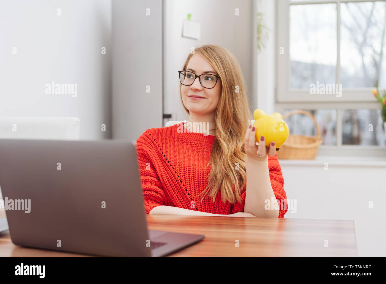 Thoughtful young woman holding a yellow piggy bank as she relaxes at a table at home looking up with a smile as she imagines all the things she can do - Stock Image