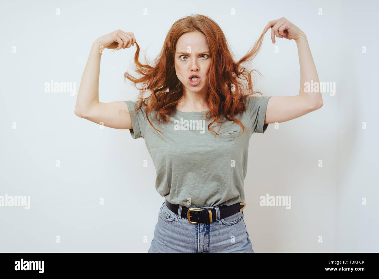 Frustrated young woman pulling at her long red hair snarling and look cross eyed at the camera in front of a white wall with copy space - Stock Image