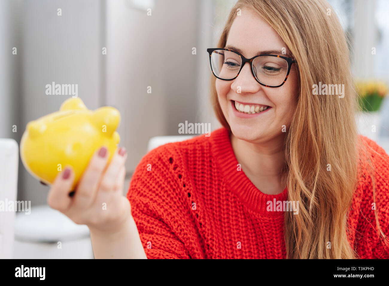 Young woman looking at her piggy bank with a pleased smile as she imagines everything she can do or achieve with her savings - Stock Image